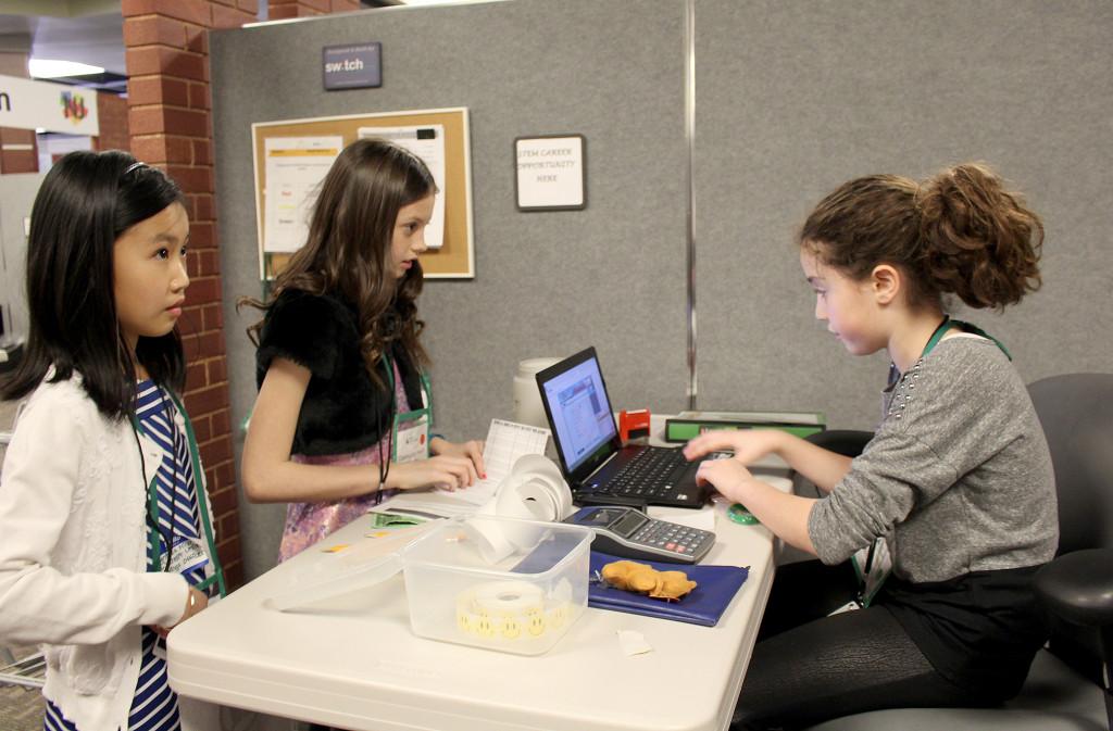 "(above) Central 5th grader Samara Harmatz (R), ""sales manager"" for Walmart assists customers Cynthia Ming and Kayla Cullinane."
