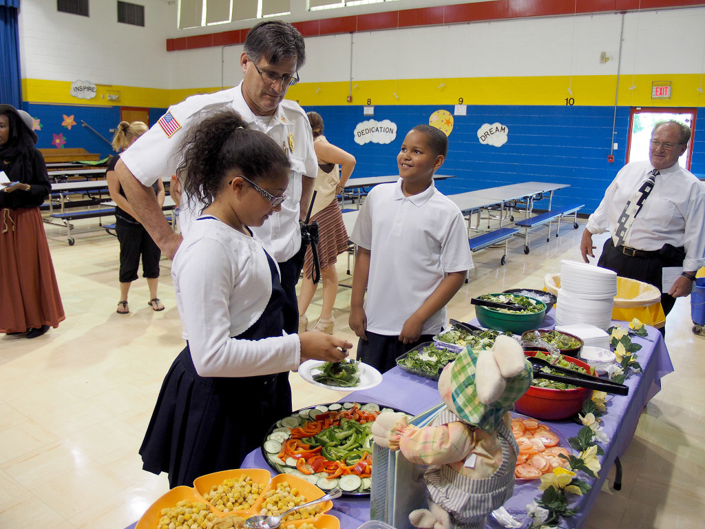 """(above) Students Jocelyn Nova, Linden Fire Chief Joseph Dooley, and Kyle Gutierrez make a salad together. Jocelyn said """"We invited the firefighters to eat a healthy salad with us because they in the beginning of the year they were strangers and they are now our friends. """"Kyle told the Chief that firefighters are important because they help, even if they are at recess and they have a disagreement they will still save your life. That is being a good citizen and good character."""