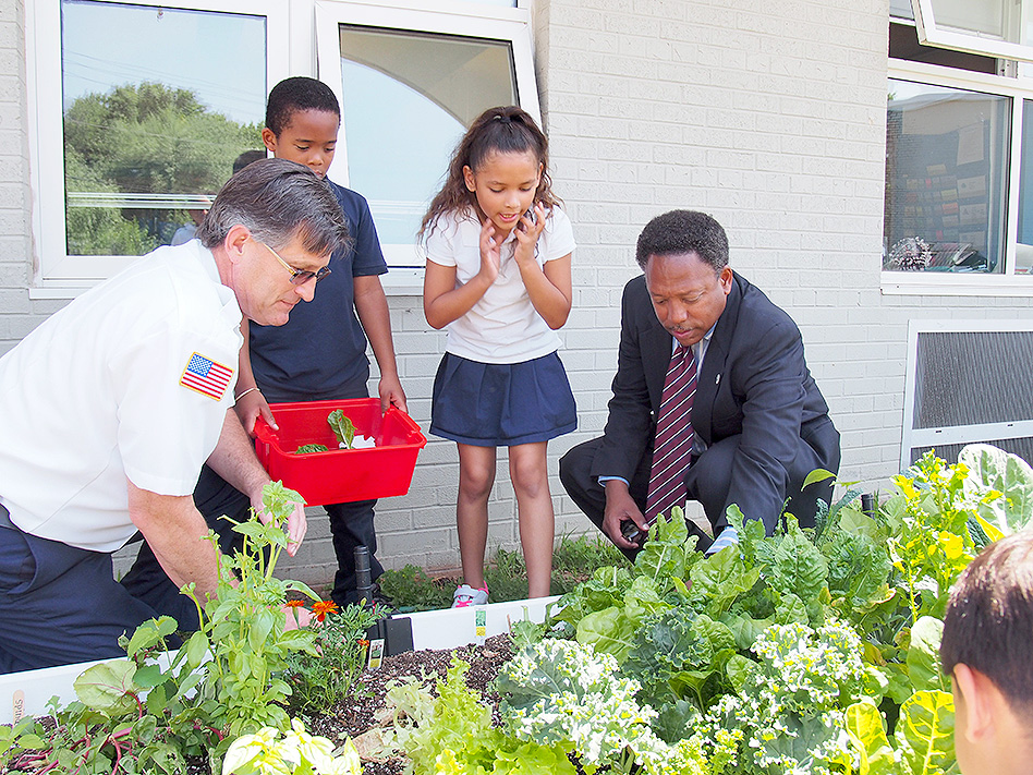 (above) Fire Chief Dooley picks lettuce as Daryl Agyei holds the bowl. Daryl was watching with a cautious eye and reminds the Chief to be gentle and snap off each mature leaf, leaving behind those that aren't ready so they can grow bigger for another day. His classmate Gabriella DeCampos explains to Mayor Armstead that it is important to have a garden because we can keep growing up healthy, and learn where the food comes from. She described how they planted the garden from seedlings, and they watered it. It took a lot of work.
